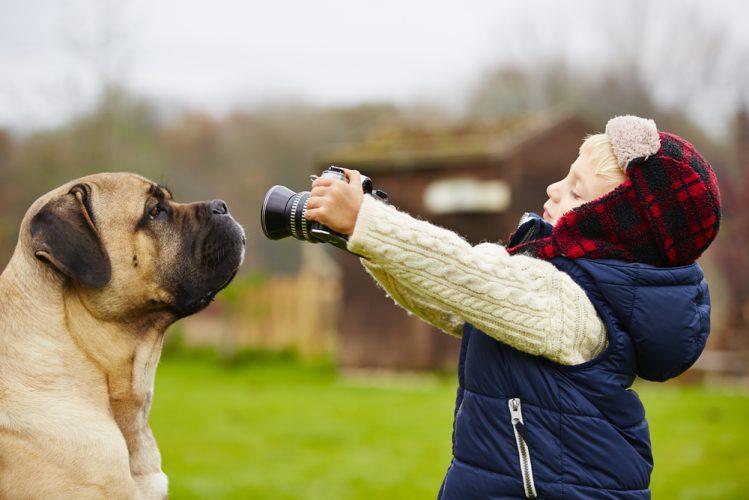 犬にカメラを向ける少年