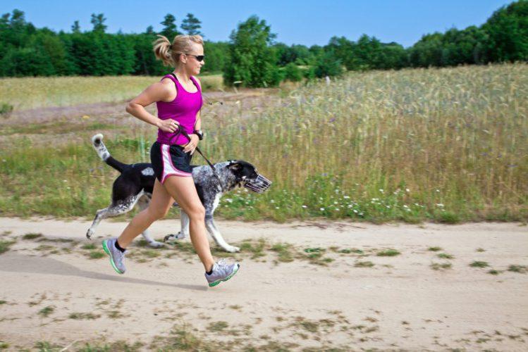 砂上を走る飼い主と犬